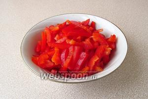 Плод сладкого перца вымыть, разрезать вдоль на 4 части, удалить плодоножку и семяносцы с семенами, а затем каждую четвертинку тонко нашинковать поперёк.