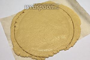 Раскатать тесто на бумаге для выпечки в круг, на пару см больше диаметра формы для выпечки.