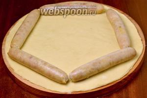 Укладываем колбаски по краю круга и оборачиваем их тестом, формируя валик.