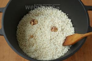 Головки чеснока очистить от верхней кожуры и сполоснуть водой, воткнуть в рис. Налить в казан горячей воды столько, чтобы она покрыла рис сверху на 1-1,5 см. Варить с открытой крышкой пока рис впитает в себя всю воду.