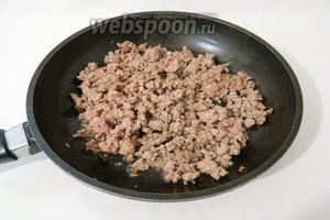 В сковороде нагреваем подсолнечное масло, высыпаем фарш и готовим на среднем огне. В процессе готовки периодически разбиваем деревянной лопаткой образовавшиеся комочки из фарша.