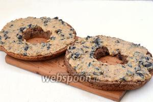 Смазать нижний и средний пласт молочным кремом с черносливом и орехами.