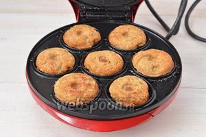 Аппарат для приготовления пончиков разогреть и выложить в каждую ячейку по полной столовой ложке теста. Закрыть крышку и выпекать до готовности (2-3 минуты). Можно выпекать и в виде оладьев на сковороде с подсолнечным маслом.