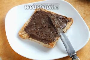 Немного остудите хлеб и смажьте два ломтика шоколадным маслом.