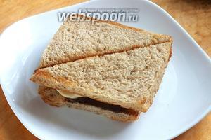 Накройте бутерброды оставшимися кусочками хлеба и разрежьте по диагонали.