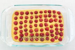 В форму, застеленную пекарской бумагой, выкладываем тесто. Поверх него — малину. Если у вас заморженная ягода, то её размораживать не нужно. Размер моей формы 17,5х28 см. Выпекаем в разогретой до 180ºC 40-50 минут.