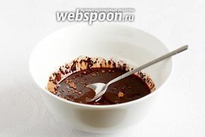 В ёмкость высыпать какао и залить горячим маслом. Размешать до полного объединения.
