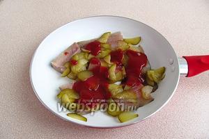 Сельдь посыпать солёными огурцами и полить томатом.
