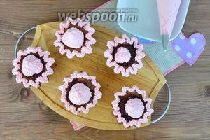 Розовым кремом с помощью кондитерского конверта украсить серединку и более тонкой насадкой край корзинки.