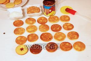 Намазать 1 половику печенья (примерно 1 кофейная ложка на печенюшку) сгущёнкой, накрыть второй половинкой, слегка прижать, чтобы по бокам выступила сгущёнка и обвалять края в кокосовой стружке и орешках.