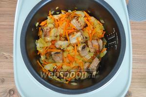 Добавить к рёбрам нарезанный лук и морковь, натёртую на тёрке, и обжарить 10 минут.