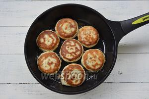 Налейте на сковороду немного растительного масла и обжарьте на нём сырники с двух сторон под крышкой.