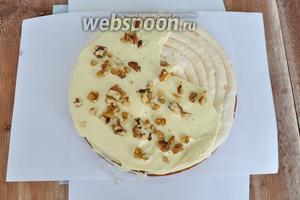 Приступим к сборке торта. На тарелку (у меня доска) выкладываю 4 листа бумаги, по одному с каждой стороны. После сборки торта бумагу удалю и тарелка останется чистой. На песочный корж нанести крем и посыпать орешки. Положить корж безе, нанести крем и орешки.