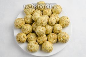 Отделяя небольшое количество теста, скатать шарики размером с грецкий орех. Обернуть пищевой плёнкой. Поставить тарелку с заготовками в морозильную камеру на 20-30 минут.