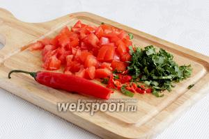 Тем временем нарезать мелким кубиком помидоры, измельчить перец чили и кинзу.