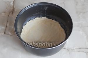 Кастрюльку мультиварки смазываем небольшим кусочком сливочного масла. Переносим в неё одну лепёшку из теста, немного приминаем пальцами и делаем бортики сантиметра 3-4.