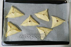 Готовые треугольники выкладываем на противень с пергаментной бумагой.