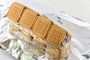 Сформировать массу треугольником и прикрепить в виде крыши домика 8 штук печенья. Печенье надо предварительно окунуть в тёплое молоко.