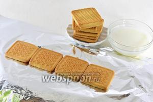 На кухонную доску выложить фольгу. На фольгу выложить в один ряд 4 штуки печенья, предварительно обмакнув его в  тёплое кипячёное молоко.