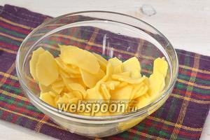 Картофель очистить, помыть и нарезать очень тонкими пластинками — лучше для этого воспользоваться специальной тёркой или картофелечисткой.