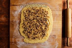 Посыпьте тесто орехами, стараясь распределять их равномерно.