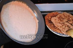 Очень горячую сковороду смажем малым количеством сливочного масла и наливаем половник теста. Сковороду сразу наклоняем в разные стороны, тем самым даём тесту вольно растечься по дну.