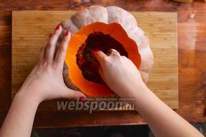 Теперь счистите с крышки волокнистую мякоть и семечки. Отложите крышку в сторону и очистите середину тыквы от мякоти и семечек. Удобнее всего это делать ложкой для мороженного или ножом для грейпфрутов.