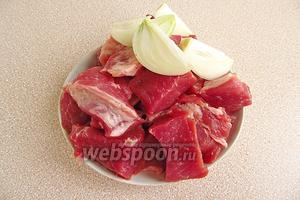 Приготовление начинки. Мясо порезать небольшими кусочками. Луковицу очистить, вымыть и разрезать на 4 части.