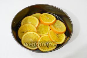 Форму для выпечки (у меня диаметр 22 см) смазываем сливочным маслом. Из остывшего сиропа вынимаем апельсины и выкладываем ими дно формы.