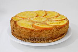 Готовый пирог охлаждаем в фориме для выпечки. Затем извлекаем из неё и переворачиваем вверх апельсинами. Нарезаем на порции и подаём. Приятного чаепития!