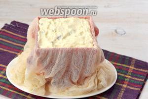 Форму для пасхи выложить влажной марлей так, чтобы не было складок. Заполнить форму творожной массой, а саму форму выложить на тарелку для стекания жидкости.