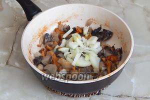 Пока лишняя влага из грибов выпаривается, очищаем луковицу и нарезаем её четверть кольцами. Добавляем к грибам и жарим всё до тех пор, пока лук и грибы не приобретут хрустящую текстуру. Не пережарьте!