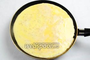На разогретой на среднем огне сковороде, диаметром 26 см растопить 1 ст.л топлёного масла. Аккуратно вылить половину яичной смеси, распределяя её тонким ровным слоем. Жарить на среднем огне минуты 2.