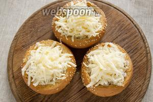 Наполнить булочки смесью грибов с луком и сметаной. Посыпать сыром, натёртым на крупной тёрке.