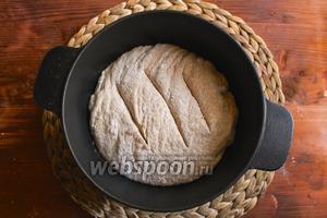 Достаньте из духовки сильно разогретую кассероль, снимите крышку и бережно переложите тесто в кассероль. Будьте осторожны, не обожгитесь! Быстро сделайте 3 надреза острым ножом или бритвой и накройте хлеб крышкой. Отправьте кассероль в духовку и выпекайте в течение 25-30 минут. Затем снимите крышку и уменьшите температуру в духовке до 220°C. Выпекайте ещё 20-25 минут пока хлеб не покроется потрясающей золотистой корочкой. Кстати признак того, что хлеб ещё не пропекся в центре, это пар выходящий из центра хлеба. Готовый хлеб при постукивании должен издавать полый звук.