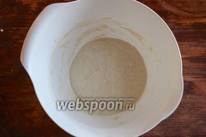 Для начала возьмите миску из стекла или пластмассы объёмом 2-3 л и высокими бортиками. Взвесьте 115 г пшеничной муки и 120 мл воды. Воду желательно брать чистую и отстоянную в течение 24 часов. Смешайте муку и воду в миске до образования однородного жидкого теста. Покройте пищевой плёнкой или заверните в пакет. По идее закваска должна созревать 24 часа при температуре 21°C. Но так как дома у нас обычно намного теплее поступите следующим образом: налейте в большую кастрюлю или миску воды комнатной температуры и поставьте в воду миску. Вода будет сохранять температурный баланс и ваша закваска не испортится.