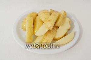 Картофель моем под проточной водой. Нарезаем на 6-8 клиньев, в зависимости от размера картофеля.