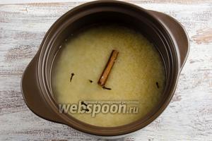 Высыпать рис в керамическую кастрюлю. Залить горячей водой, добавить корицу, гвоздику, соль и поставить на медленный огонь.