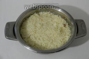 Готовим рис сначала на среднем огне до выкипания жидкости, затем огонь убавляем на минимум, кастрюлю накрываем крышкой и оставляем рис томиться ещё 10-15 минут. Огонь выключаем и готовый рис оставляем в сторону.