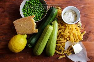 Для рецепта вам потребуется: замороженный зелёный горошек, молодой кабачок или цукини, сухая паста фузилли, цедра 1 лимона, сливочное масло, пармезан и сливки жирностью 33%.