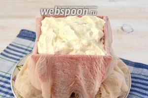 В форму для пасхи выложить слегка влажную марлю стараясь, чтобы было как можно меньше складок. Заполнить форму творожной массой.