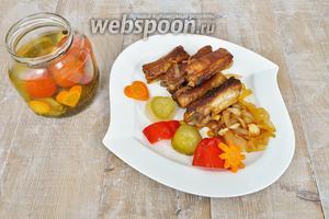 На порционную тарелку выложить немного жаренного лука и рёбрышки. Гарниром будет  овощное ассорти . Подавать немедленно.