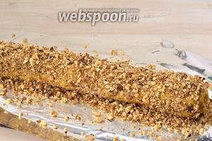 Обсыпать тесто со всех сторон орехами, вжимая их в тесто руками.