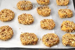 Каждый кусочек обсыпать со всех сторон орехами и выложить в форму для выпечки на кулинарную бумагу.