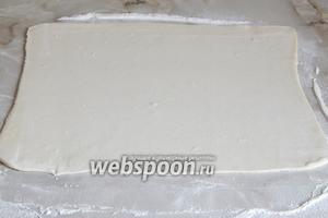 Рабочую поверхность присыпаем мукой (50 г) и раскатываем слоёное тесто (150 г). Делать это нужно по направлению в одну сторону, иначе слои просто слипнутся.