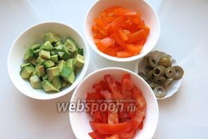Нарезаем томаты, перец, авокадо и оливки. Авокадо сбрызгиваем лимоном.