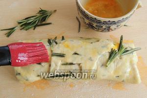 Выкладываем украшение из ягнёнка на тесто и покрываем весь рулет яйцом.