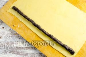 Готовое тесто разделить на 2 части. Поверхность стола подпылить мукой. Тонко раскатать в пласт, формой прямоугольника. Выдавить маковую начинку (с помощью кулинарного шприца или разложить чайной ложкой), отступив от края на 1 см.