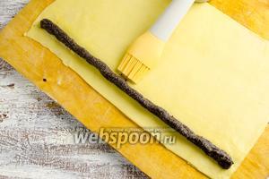 Кисточкой промазать тесто яичной намазкой за валиком маковой начинки.