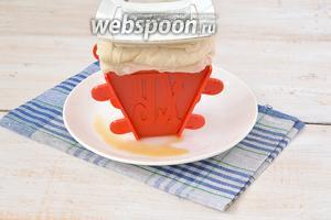 Завернуть концы марли наверх. Сверху выложить небольшую тарелку, а на тарелку — груз (пол-литровую банку с водой). Поставить конструкцию в холодильник, периодически сливая образовавшуюся жидкость.